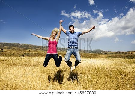 Young couple holding hands and jumping