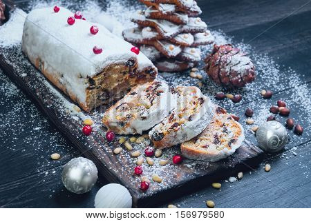Christmas stollen. Traditional German European festive dessert. Ingredients cranberries pine nuts for Christmas Stollen. Stollen cake cut into pieces. Christmas food card. Black background.