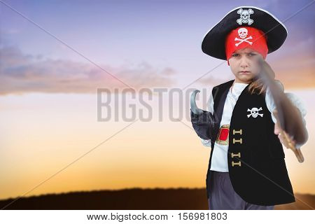 Masked girl pretending to be pirate against silhouette landscape against sky