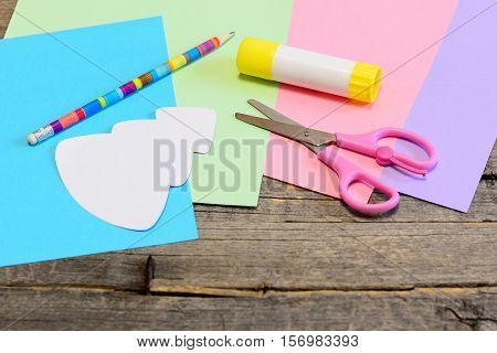Christmas card instruction. Step. Tree template, colored paper sheets, scissors, glue stick, pencil on wooden background. Easy Christmas craft idea for kids. Winter children creativity