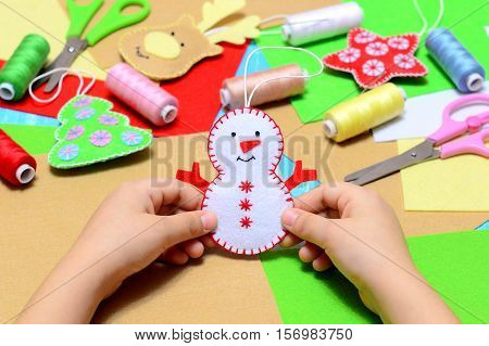 Small child holding a felt Christmas snowman in hands. Little kid shows Christmas ornament crafts. Workplace in kindergarten, school or home. Kids Christmas crafts idea. Children winter creativity