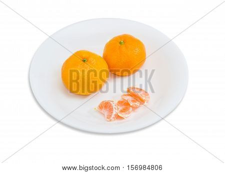 Two whole fresh ripe mandarin orange and several segments of peeled mandarin orange on a white dish on a light background