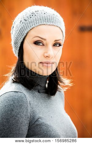 Beautiful green eyed young woman in warm clothes and gray hat smiling