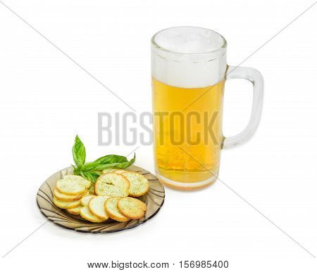 Beer glassware with lager beer rusks with basil and pesto sauce flavor and twig of basil on a saucer on a light background