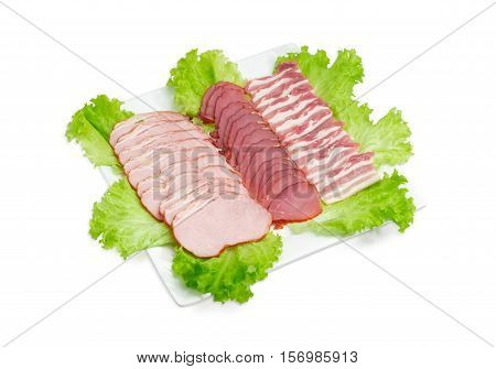 Sliced smoked pork loin cured pork tenderloin and bacon on a lettuce leaves on a square white dish on a light background