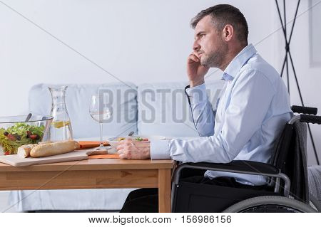 Pensive and sad man on a wheelchair is sitting at the dinner table
