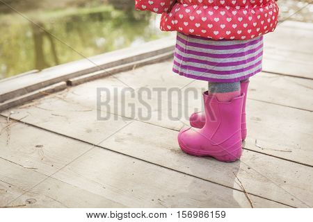 little girl in rainboots in autumn or winter nature, kids seasonal activities