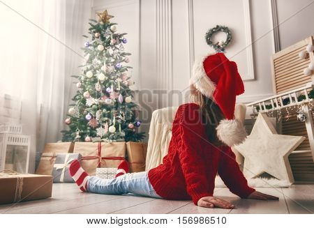 Merry Christmas and Happy Holidays! Cheerful cute little child girl with present. Kid sitting near Christmas tree indoors.