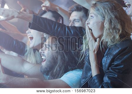 Young woman standing in a crowd of excited people at a rock concert