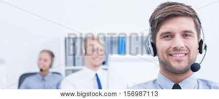 Telemarketing staff with handsets sitting at work