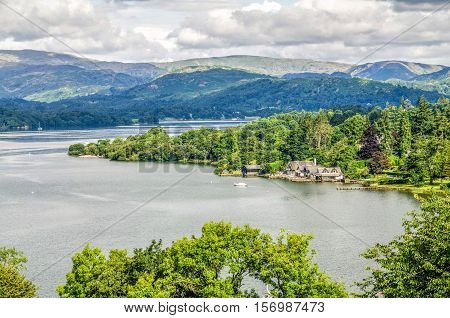 Lake Windermere in the English Lake district showing a tranquil bay with jetty cottages and a boathouse, trees and distant hills.