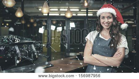 Portrait of barista wearing santa hat against snow falling