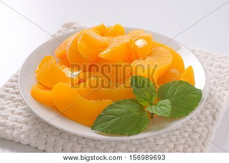 plate of peeled and sliced peaches on white table mat - close up
