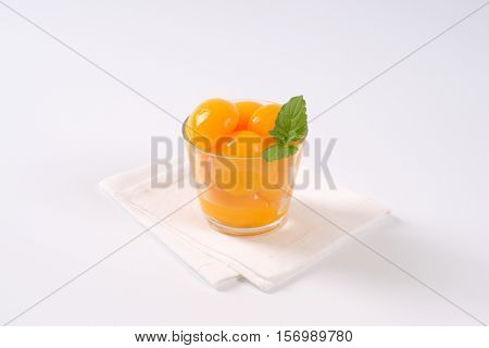 glass of peeled and halved peaches on white place mat