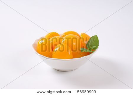 bowl of peeled and halved peaches on white background