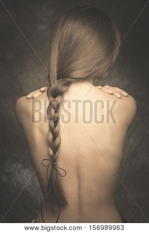 intimate woman portrait bare back and long braid studio shot