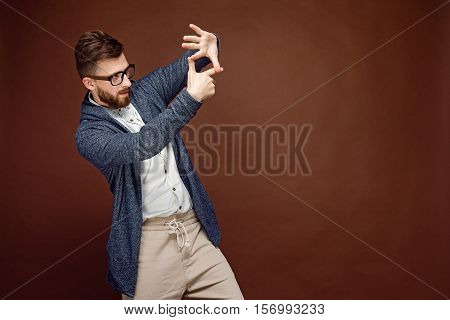 Young casual man putting hands in gesture of camera and pretending to make picture on brown background.