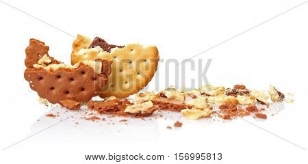 Tasty cookies and crumbs on white background