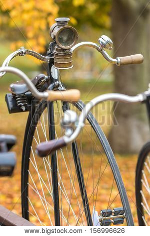 A penny farthing bicycle with an old headlamp in a park with fallen autumn leaves
