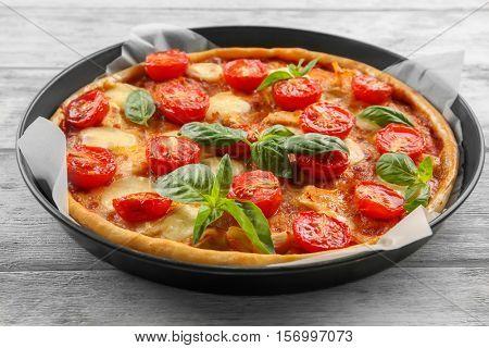Baking dish with fresh tasty pizza Margarita on wooden background