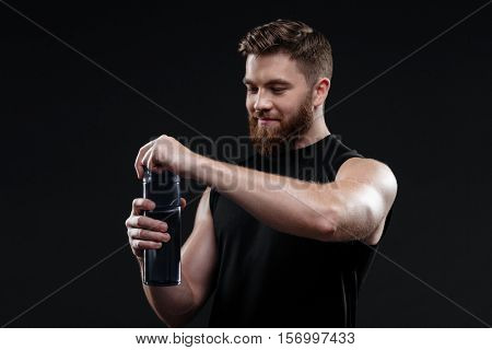 Young athletic man with bottle. open bottle. isolated dark background