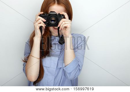 Portrait of cute redhead photographer woman wearing blue striped shirt smiling with happiness and joy while posing with camera against white studio background.