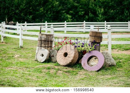 Few old Millstone from the windmill surrounded by flowers. Beautiful rural landscape. Background is a corral for horses.