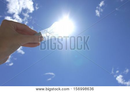 Hand holding light bulb on a background sky and sun. An abstract idea on the topic of electricity of solar energy.