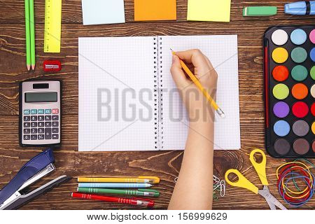 Opened Blank Notebook, Hand With A Brushwith Frame Of School Supplies Over A Wooden Desk Background.