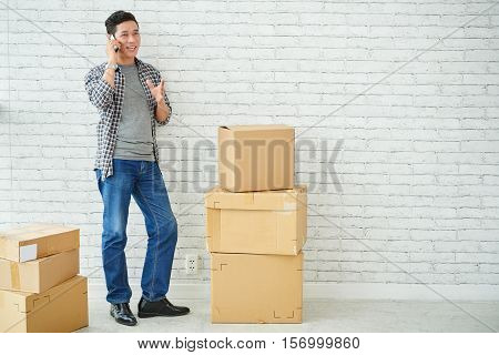Vietnamese man with cardboard boxes calling on the phone