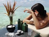 beautiful woman getting spa treatment at daylight near the ocean