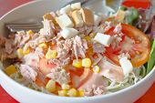 Tuna salad with vegetables on white bowl poster