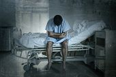 young desperate man sitting at hospital bed alone sad and devastated suffering depression crying at clinic for serious disease diagnose worried in fear on grunge dirty background poster