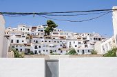 Mediterranean whitewashed tiered homes with sky discected by low powerlines Altea Alicante Spain poster
