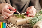 Woman's hands wrapping christmas holiday handmade present in craft paper with twine ribbon. Making bow at xmas gift box decorated with snowflake. Scissors on white wooden table poster