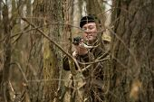 a military man in the woods with a Kalashnikov assault rifle autumn forest with no leaves green form poster