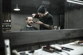 Peerless barber with a beard and a tattoo is cutting the hair of his bearded client in the barbershop. He is using a cutting comb and a hair clipper. Customer has hairgrips on the head. Horizontal. poster