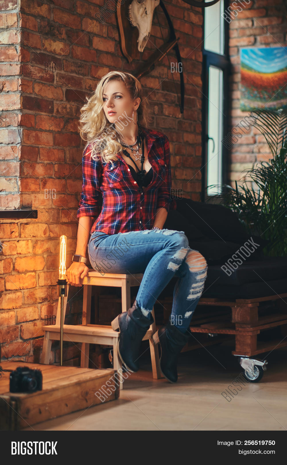 9d6314b93fd Sensual Blonde Hipster Girl With Long Curly Hair Dressed In A Fleece Shirt  And Jeans Holds