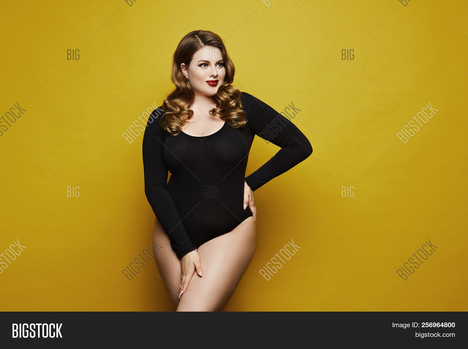 181125186e820 Plus size sexy model, fashionable blonde girl with bright makeup, in black  bodysuit, with stylish hairstyle, smiling and posing at yellow background  in ...
