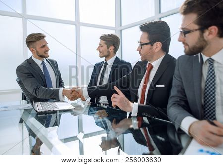 handshake financial partners over the negotiating table.