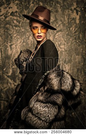Portrait of a beautiful woman in luxurious fur coat posing in studio. Luxury, rich lifestyle. Fashion shot.