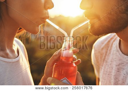 Sharing Drink. Close Up Of Young Couple Drinking From One Bottle With The Drinking Straw While Spend