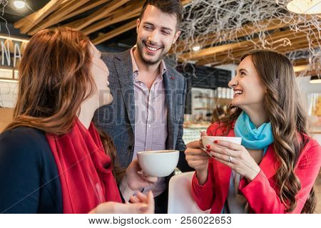 Attractive young woman meeting an old friend while sitting and enjoying a hot drink together with her best friend in a trendy coffee shop