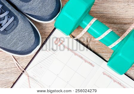 Calendar Plan With Green Dumbbell And Sneakers On Wooden Background. Workout Plan Concept.