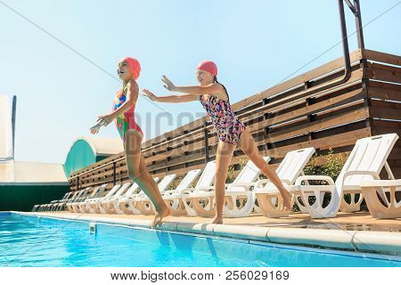 The Portrait Of Happy Smiling Beautiful Teen Girls Jumping At The Swimming Pool. Little Child At Blu