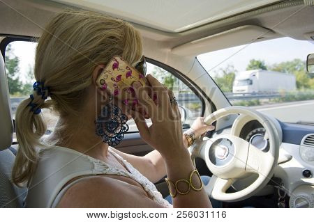 Bottrop, Germany - Aug 16, 2018: A Blond Woman Is Calling With Her Smartphone While She Is Driving O
