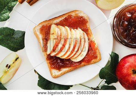 Toast With A Crushed Apple Jam, Slices Of Fresh Apples, Cinnamon On A Plate On A White Table. Apples