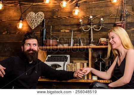 Happy Couple Or Marriage Looking Each Other Laughing And Holding Hands Sitting At Home. Couple Spend