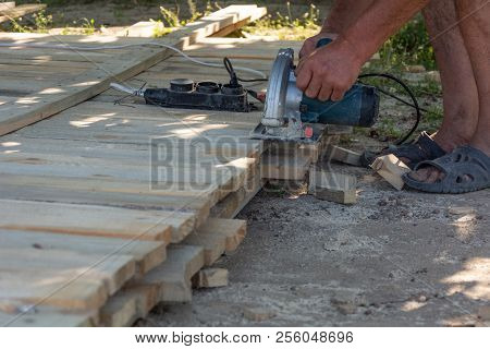 Carpenter Using Circular Saw For Cutting Wooden Boards. Construction Details Of Male Worker. Formwor
