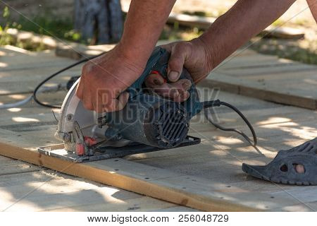 Carpenter Cuts A Board Manual Electric Saw ,close-up , Concept Building And Repair. Formwork For The